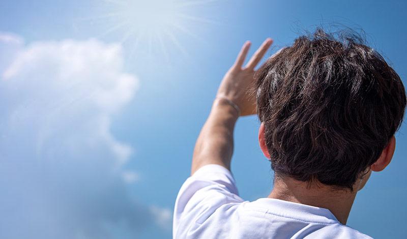 日差しに手を掲げてまぶしそうにする男性
